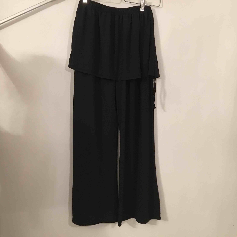 Mjuka byxor med utsvängda ben och en påsydd kjolsdel. ej angivet tillverkare eller storlek men bör passa M. Köpare står för frakt.. Jeans & Byxor.