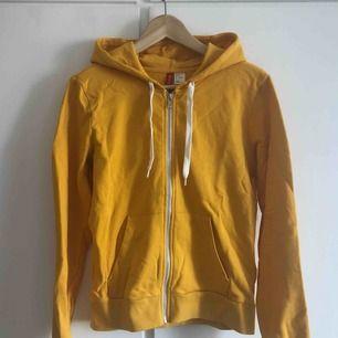 Oanvänd gul hoodie med två fickor från H&M Divided.