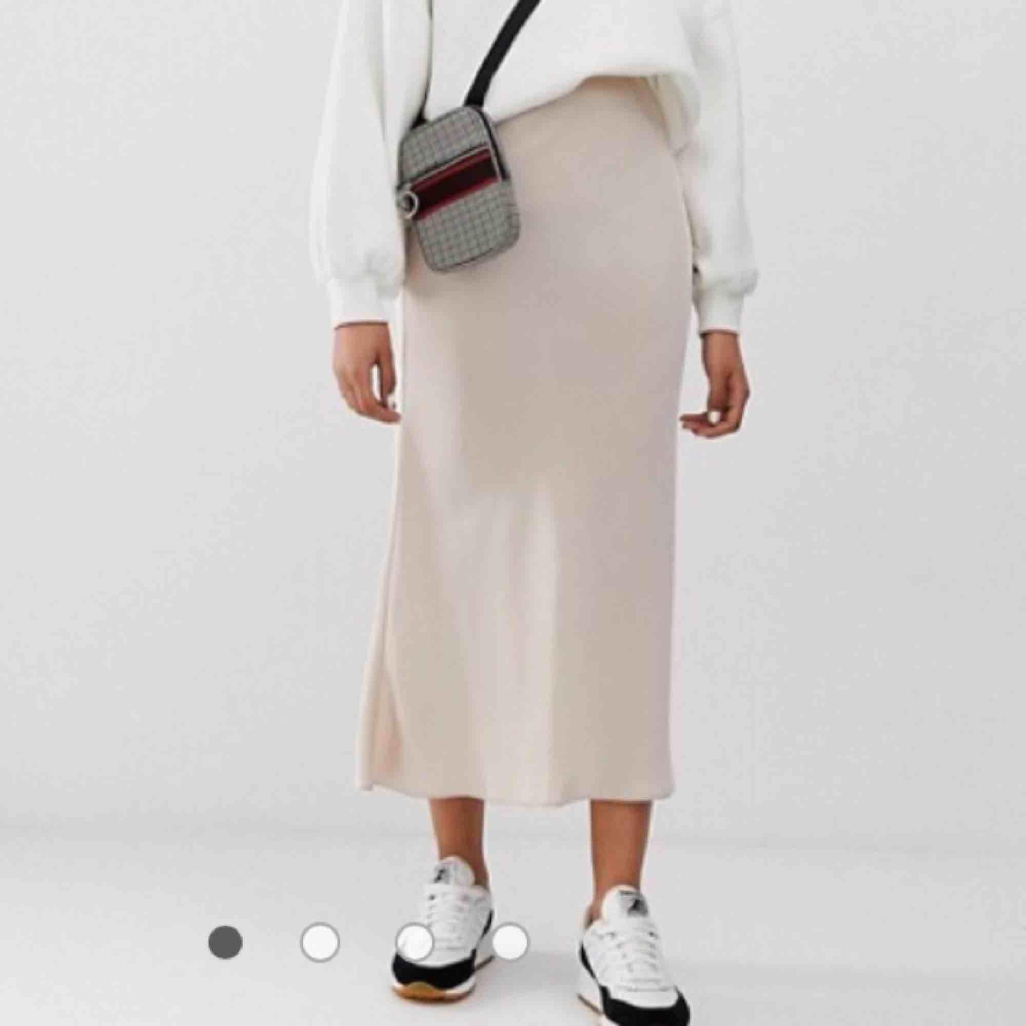 """Slip siden kjol från Asos Design. Aldrig använd förutom på bilderna! Sitter superfint och smickrande midi längd. Går att både klä upp och ner till vardags🖤🥀 Sista bilden är från hemsidan. Färgen heter """"off white"""". Kjolar."""