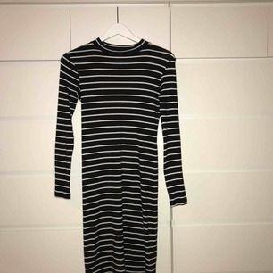Svart/vit randig klänning från H&M. Har en liten polokrage. Frakt ingår i priset.
