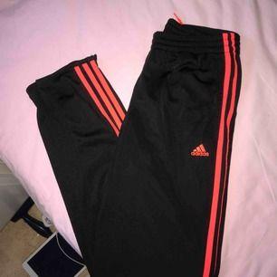Ett par svarta Adidasbyxor med oranga sträck, knappt använda 🥰