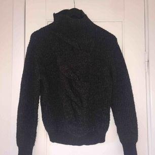 Varm tröja med polokrage. Stickat mönster på framsidan.