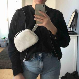Superfin väska som man kan ha runt mage/axel som på bilderna men det medföljer även ett band så att man kan ha den som en vanlig axelremsväska. Vitare än den ser ut på bilderna! Perfekt nu till vår och sommar