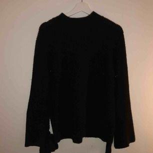 Jättefin svart stickad tröja med knytning längst ner i ärmarna