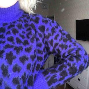 En oversized jättemysig stickad tröja i en mörkblå färg. Tröjan har sjukt snyggt leo mönster och en hög krage. Tröjan kommer ifrån nakd