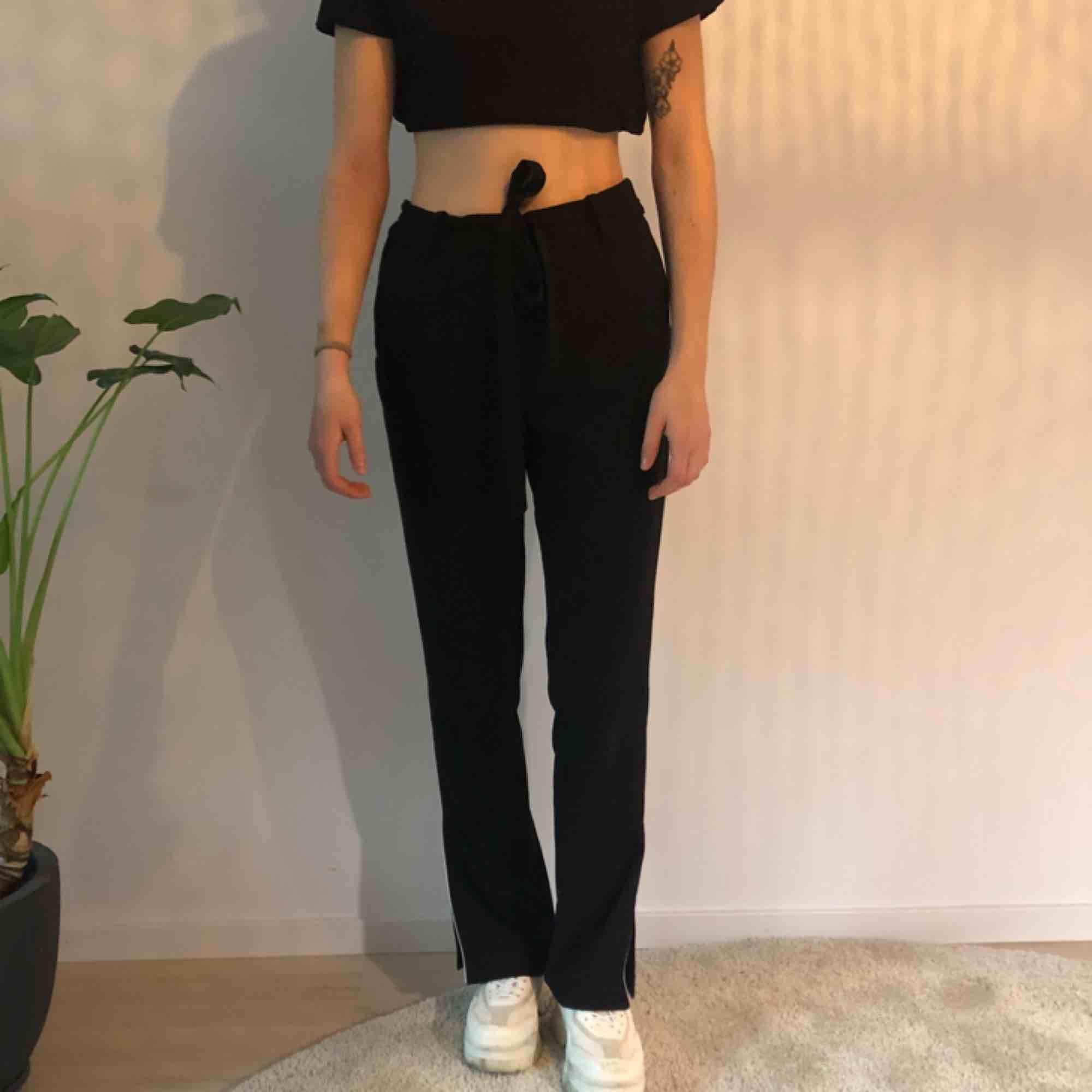 Svara byxor med vit rand och slits i sidan från monki Använda men i bra skick. Jeans & Byxor.