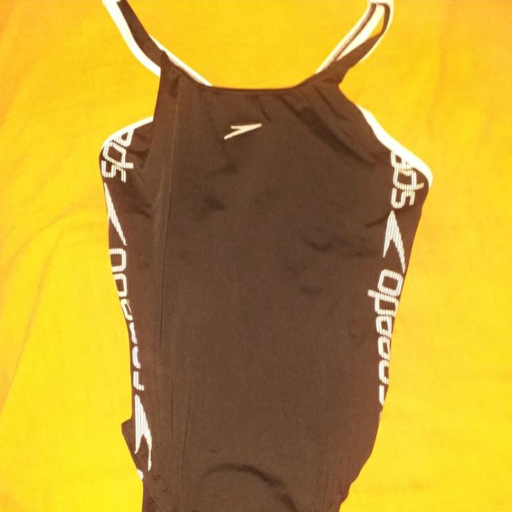 En svart baddräkt med vit text längd ner 51cm axelband 13cm. Övrigt.