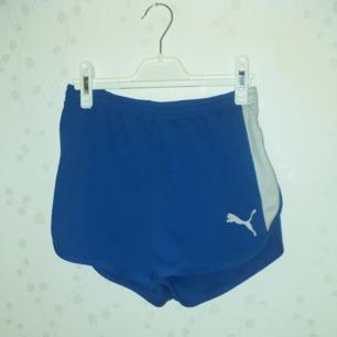 Ett par blå puma shorts som är material som en lite tjockare tygg som en baddräkt (platt) midja 32 cm längd ner 34 cm sidorna 24 cm