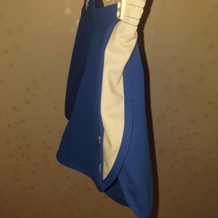 Ett par blå puma shorts som är material som en lite tjockare tygg som en baddräkt (platt) midja 32 cm längd ner 34 cm sidorna 24 cm. Shorts.