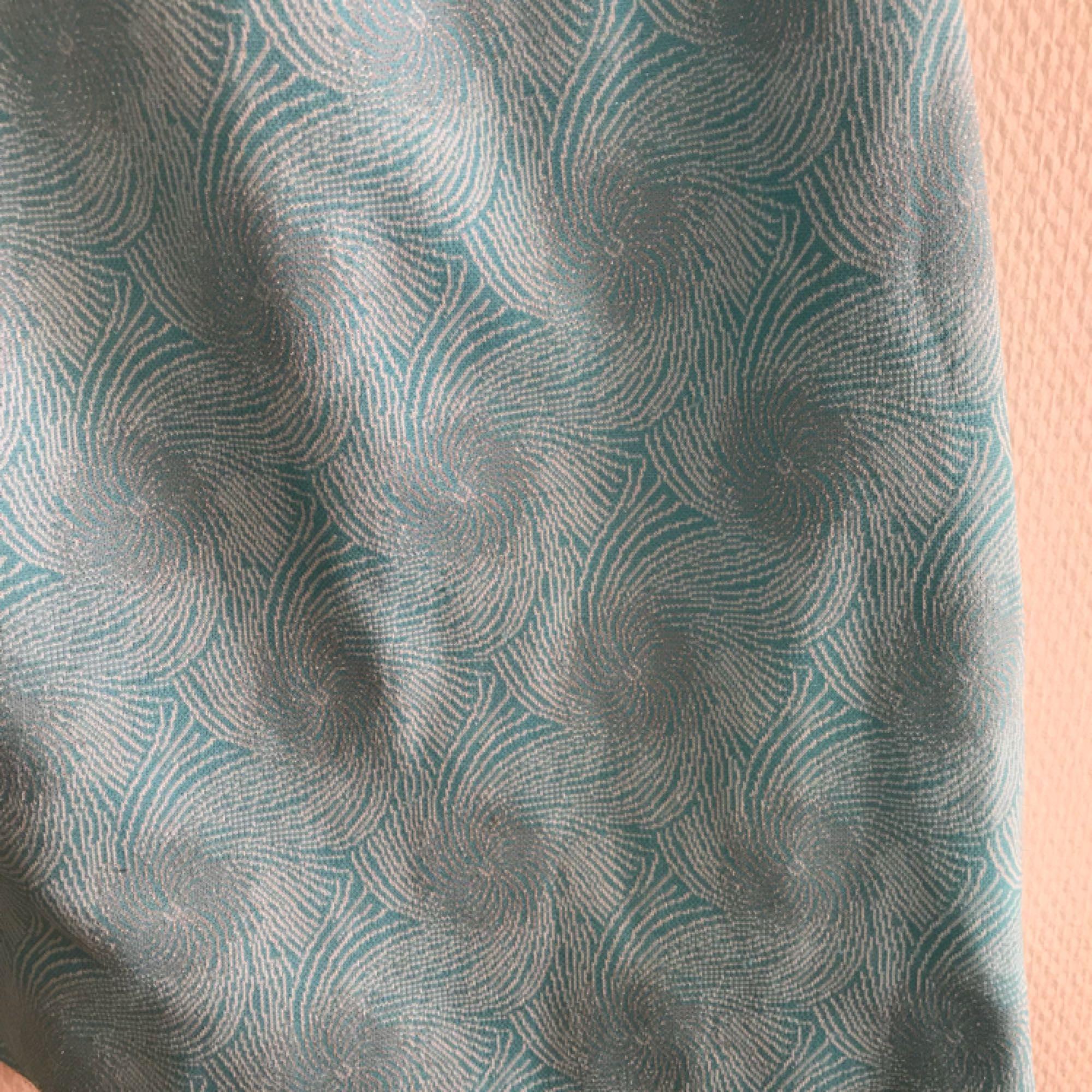 Blå kjol med mönster som glittrar. Fint skick, första bilden stämmer bäst överens färgmässigt!🐬 frakt tillkommer på 36kr . Kjolar.