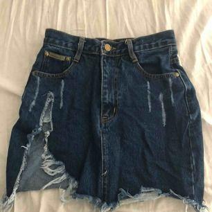 Jeans kjol, tight upptill. Slits på sidan av benet