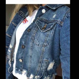 Jeansjacka med slitningar. Kort modell med lite puffärm.