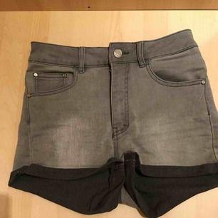 Gråa jeans- shorts. Högmidjade och sitter ganska tight.
