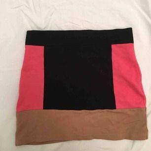 Tubkjol med en tjock rosa rand på varje sida, även en beige rand rund hela kjolen.