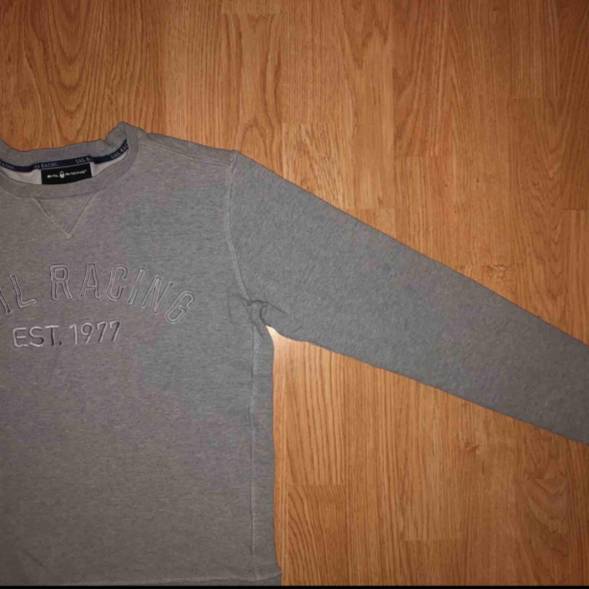 Sail Racing est. 1977 college tröja.  Grå i färg. Stämmer i storlek. Huvtröjor & Träningströjor.