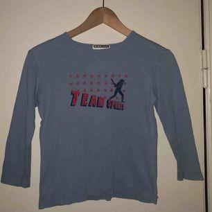 Trekvartsärmad tröja från Giordano i storlek S. Har ett litet hål vid trycket, syns knappt dock  Kan fraktas men då står köparen för frakten