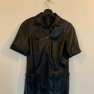 Helt oanvänd svart skinnklänning med knappar och två fickor framtill.
