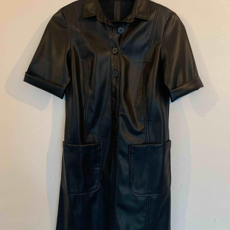 Helt oanvänd svart skinnklänning med knappar och två fickor framtill. . Klänningar.