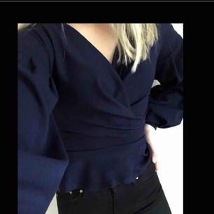 Marinblå blus med ballongärm och knytband i ryggen/midjan.