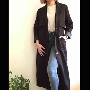 Lång kappa/ jacka i färgen svart som endast är använd runt fem gånger och i mycket fint skick.  Plagget har två fickor, avtagbart bälte och slits där bak.Nypris 600kr Frakt står köparen för