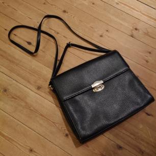 Vintage svart väska med silverdetaljer i fint skick! Någorlunda liten och smalt boxig i modellen, rymmer trots det ganska mycket!