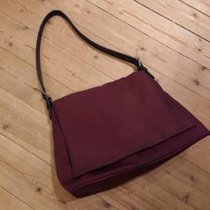 Vinröd väska från Coach i mycket fint skick! Är i lagom storlek och rymmer hyfsat mycket!