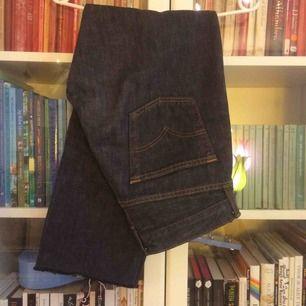 Ett par mörk blågråa Levi's jeans med knappar i stället för gylf, väldigt bra skick med rough cut i byxben slutet