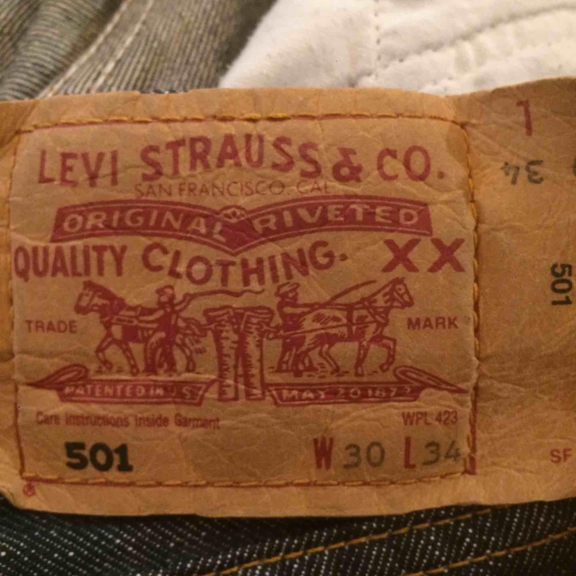 Ett par mörk blågråa Levi's jeans med knappar i stället för gylf, väldigt bra skick med rough cut i byxben slutet. Jeans & Byxor.