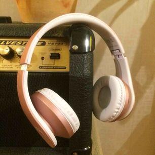 Ett par rosegold Bluetooth hörlurar med ok kvalite laddare och sladd ingår