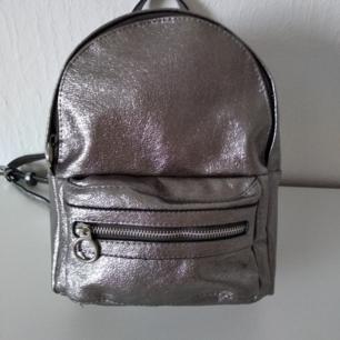 Nästan oanvänd snygg silverfärgad ryggsäck från Mango. Perfekt skick, förutom en pytteliten fläck som syns på sista bilden. Höjd: 28cm Bredd: 20 cm Djup: 10 cm
