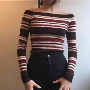 Randig off-shoulder tröja i  ljusrosa, mörkbrunt, vitt, rödbrunt och senapsgult. Är i fint skick och sitter slimmande på.       Frakt står köparen för!