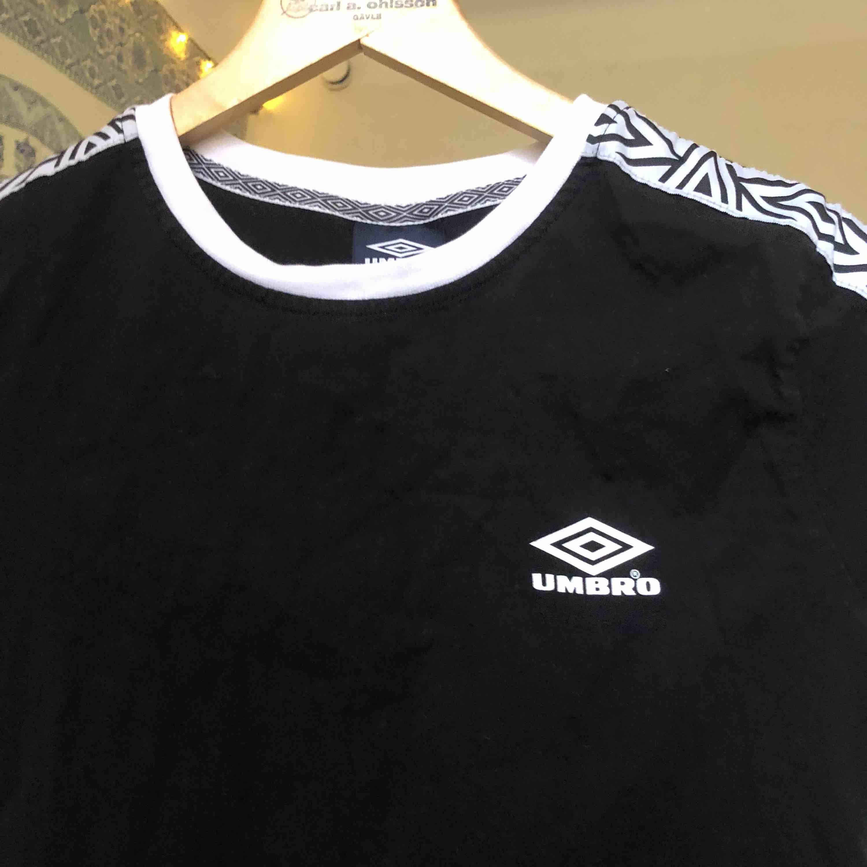 En svart tröja med vita detaljer från Umbro men köpt från ASOS. Möts upp på Södermalm i Stockholm eller fraktar. Köparen står för frakten :) . T-shirts.