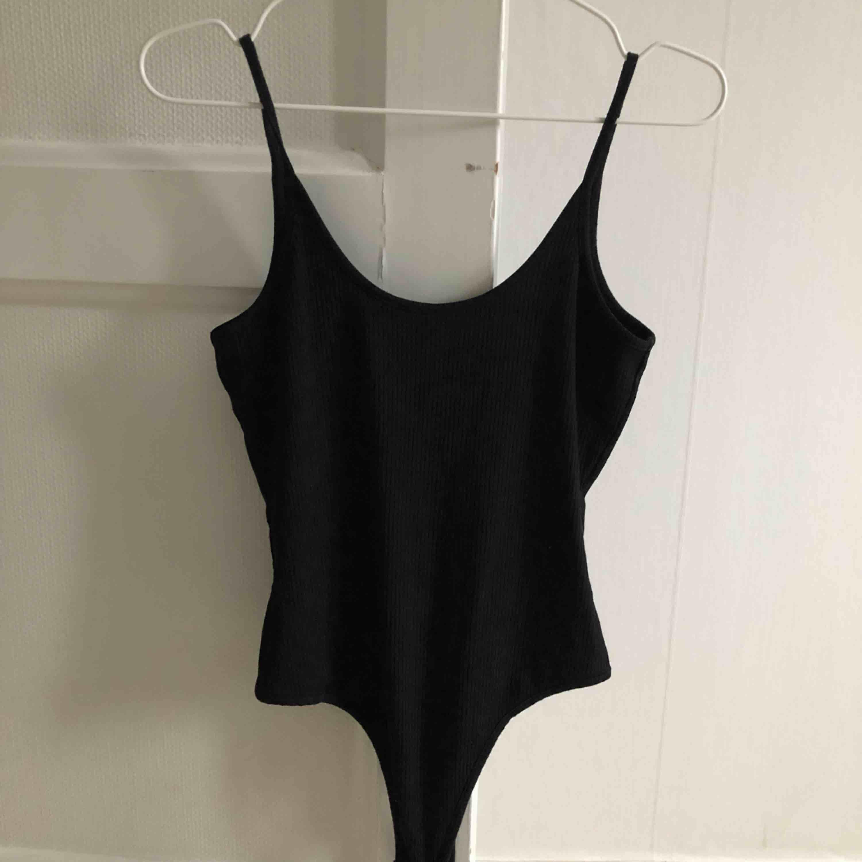 snygg basic svart bodysuit från Ivyrevel. Fin detalj med öppen rygg, perfekt inför sommaren☀️ Använd fåtal gånger. (OBS, pris inkluderar frakt) . Toppar.