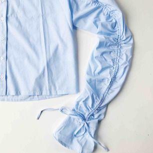 Oanvänd skjorta från Missguided. Åtdragbara ärmar med knytning. Ljusblå och vit-randig.