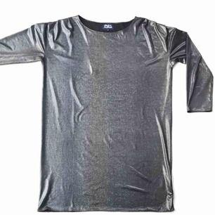 Rak klänning från Made in The Shade. Glansig/glittrig klänning som är använd 1 gång. Färgerna skiftar i blått/grönt/grått/lila beroende på ljus. Mycket gott skick.