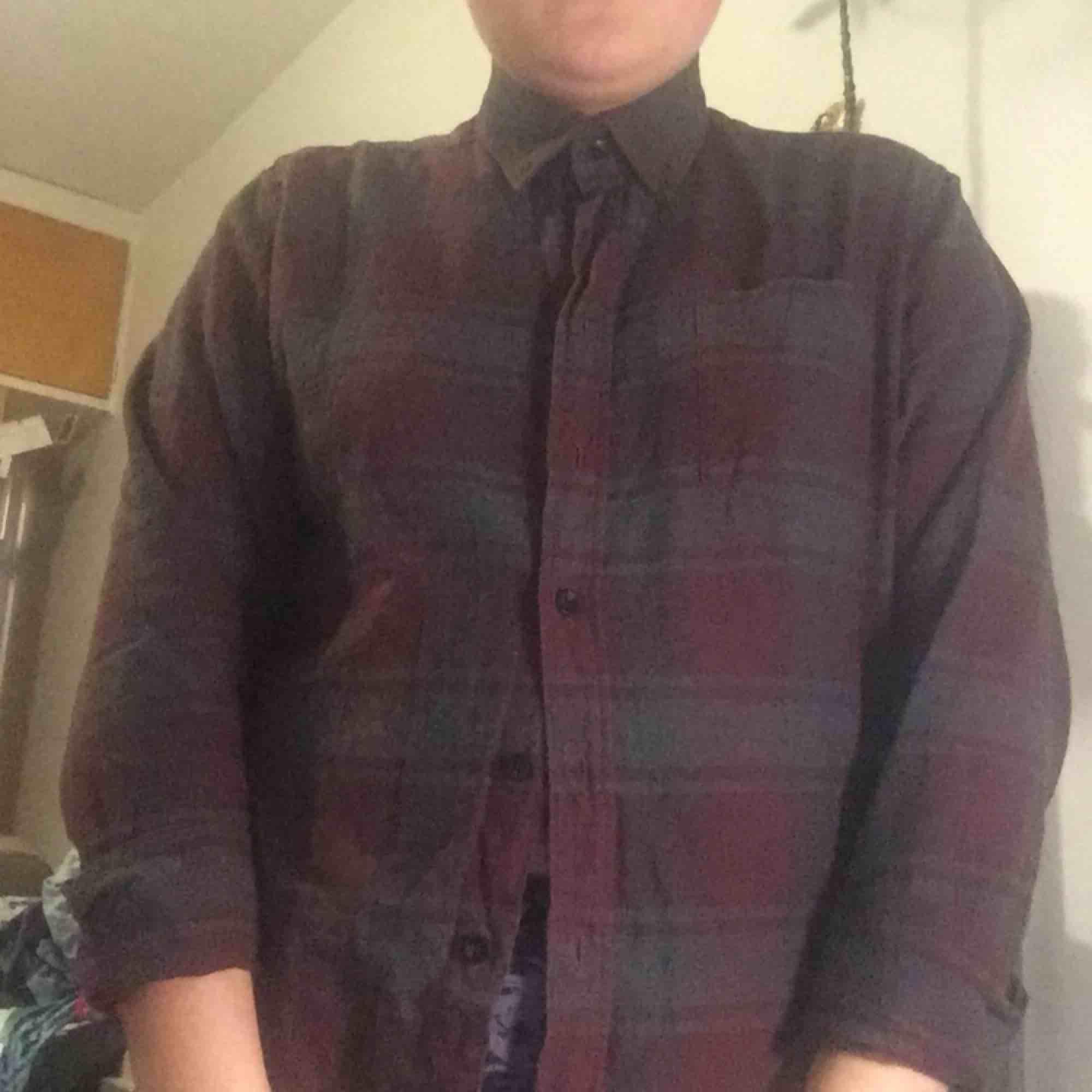 En röd/grå rutig flanellskjorta . Skjortor.