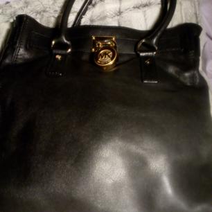 Michael Kors Hamilton, aldrig använd, bara legat i garderoben, axelband finns, svart skinn, passa på att fynda mina väskor till ett mycket bra pris. Väskan är naturligtvis äkta med id-nr!!!!