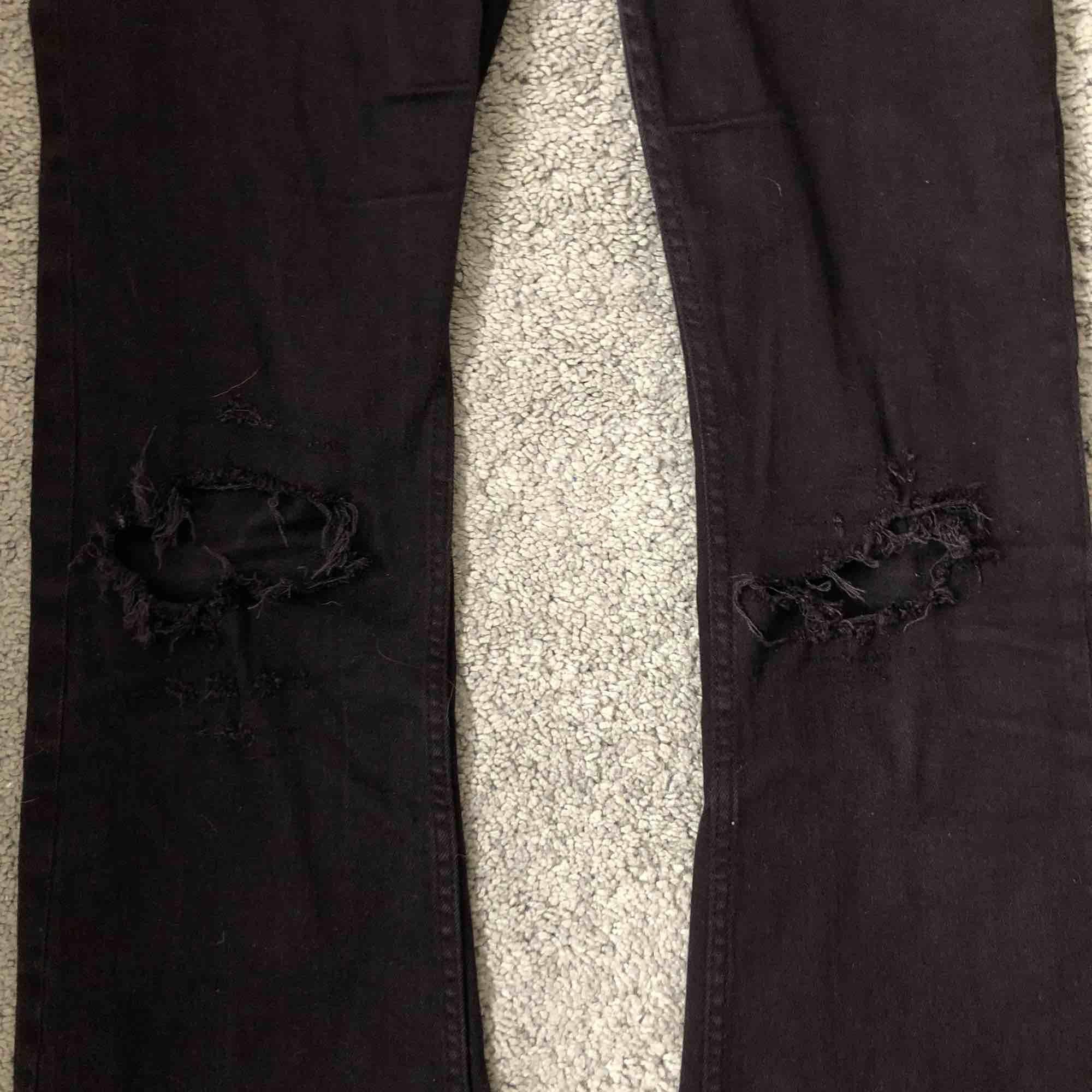 Nästan helt oanvända svarta bootcut jeans med egen gjorda hål på knäna!  De ser lite rödaktiga ut på bilderna men i verkligheten är de svarta!!. Jeans & Byxor.