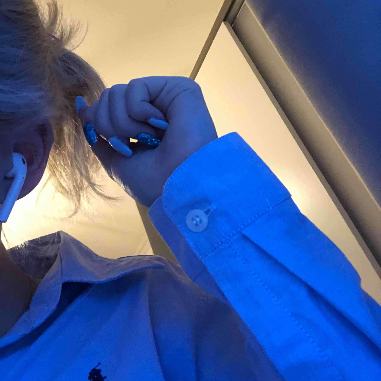 Ljusblå Ralph Lauren skjorta i nyskick (dammodell) storlek M men sitter bra på mig som är S och passar nog XS också väldigt bra. Fin passform och cool att styla. NYPRIS 995kr. Skjortor.