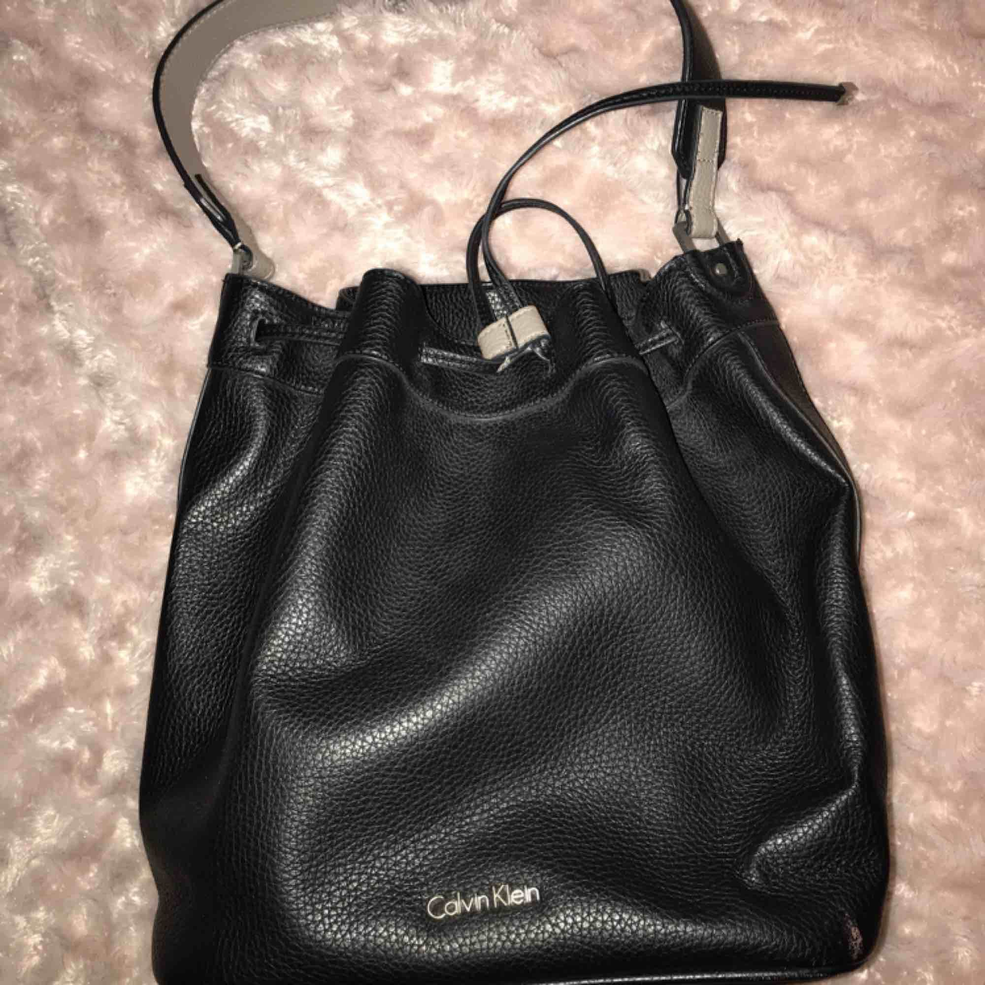 Calvin Klein väska. Handtaget är lite slitet annars är den i bra skick. Väskan har 3 fack inuti, ett med dragkedja. Köpte den för ca 1500kr. . Väskor.