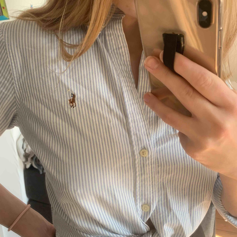 Blå/vit randig Ralph Lauren skjorta i storlek M. Skjortor.