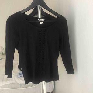 Fin långärmad tröja med detaljerat mönster i mitten.