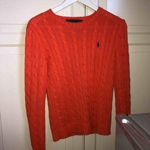 Jättefin orange kabelstickad tröja från Ralph Lauren.