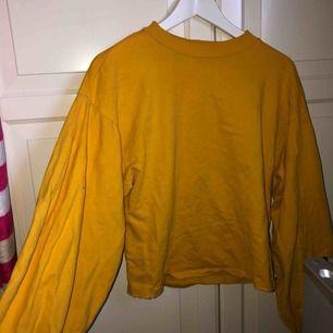 Gul långärmad tröja från Nelly med balongärmar.