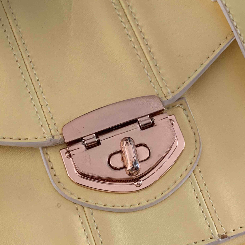 Jättefin gul väska med rosédetaljer, inköpt i London  Har några små märken men inget som märks och ger istället väskan en fin vintagelook, spännet framtill är lite bortskavt Möts i Malmö, kan fraktas om köparen står för frakten. Väskor.