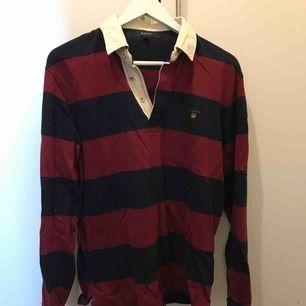 Blå och vinröd-randig rugbytröja av märket GANT. 100% bomull storlek M
