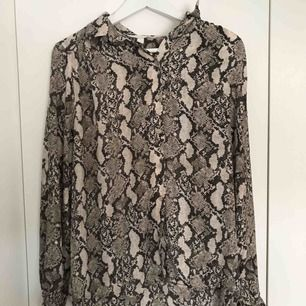 Snygg och skön snakeprint skjorta ifrån H&M använd endast 1 gång. Strl 40 så den är lätt att röra sig i och man kan ha skjortan uppknäppt utan att de ser dåligt ut (så som jag har på bilderna)
