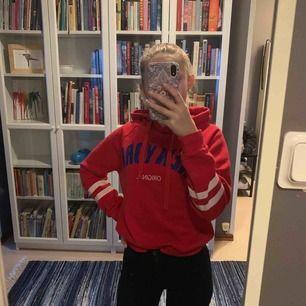 En röd hoodie med text och tryck på armarna, den är snygg och köpt för ett år sen