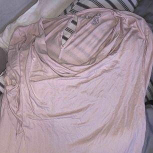 En ljusrosa tröja med lite met tyg vid bytet + frakt