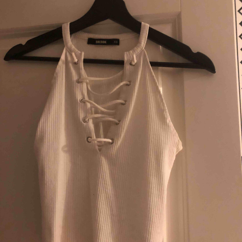 Ett fint vitt linne från bikbok i storlek XS. Har snörning vilket är en fin detalj på det hela. Använd men fint skick. Frakt kan tillkomma . Toppar.